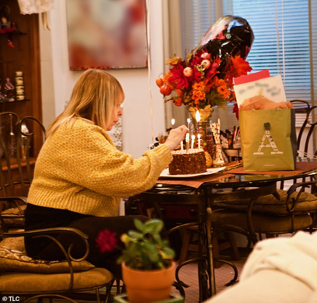 Marcia (pictured) lights candles on a cake to celebrate Alena