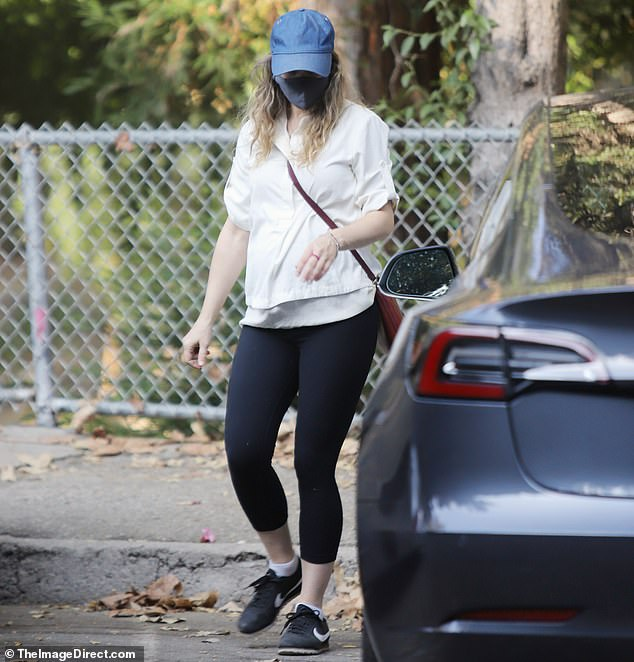 Street style: She stuck to a simple outfit of a sweatshirt and leggings, accessorizing with a blue baseball cap and a cross-body bag